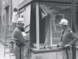 Police watch men boarding up storefront after riot, Rochester, NY, 1964