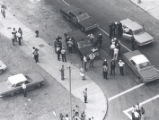 Aerial view of police and citizens gathered on unidentified corner after riots, Rochester, NY, 1964