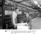View of R.K. Holm, Elec. engineer, & G.W. Goelz, V.P. & Ch. engineer, studying blue-print...