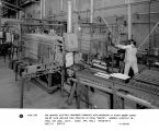 Two General Electric de-binder furnaces with operator at right shown charging #1 with nuclear fuel...