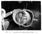 "Engineer examines special floodlight (L-101) designed for """"blanket lighting""""..."