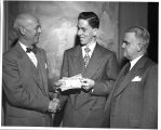 John Armstrong, local high school student, is shown receiving $125 in government bonds from Dr....
