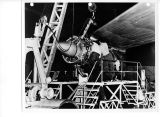 Demonstrating the ease of pod-mounted jet engine change, a Boeing Airplane Company four-man crew...