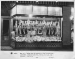 Boston Meat and Grocery Co., Night view of display window with slabs of meat