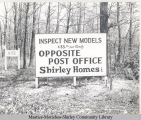"A sign reading , ""Inspect New Models $33.79 per Month Opposite Post Office Shirley Homes Inc."