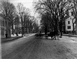 A view of Main Street in Delhi, New York, with horse drawn wagon in middle of street