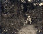 1903, Mark Twain on steps to the study seated