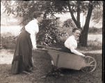 Two women, one pushing the other around in a wheelbarrow