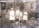 Two young girls and two boys and family dog, Bibbs in yard