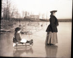 Woman in winter clothes pulling small girl on sled across the ice, building in rear