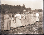 Nine women with rakes in a field