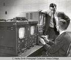 Television instructor teaching use of switching equipment to TV student, Ithaca College, Ithaca,...