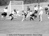 Field hockey game, Ithaca (white blouses, dark skirts) attacking opponent's goal on Ithaca field,...