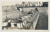 [Laden barge with woman at tiller passing under railroad truss bridge] [untitled] (1front)...